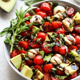 A bowl of caprese salad with avocado with basil and avocado in the background