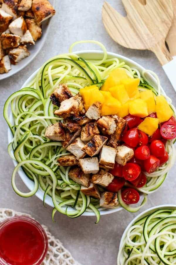 A bowl of Grilled Chicken Zoodles with BRIANNAS blush wine vinaigrette on the side