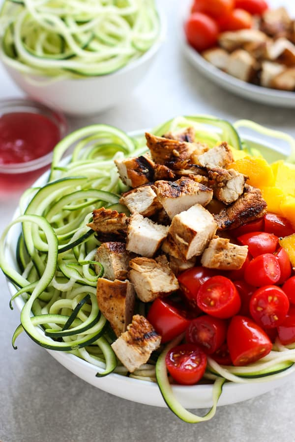 A bowl of zoodles topped with grilled chicken, mango and tomatoes
