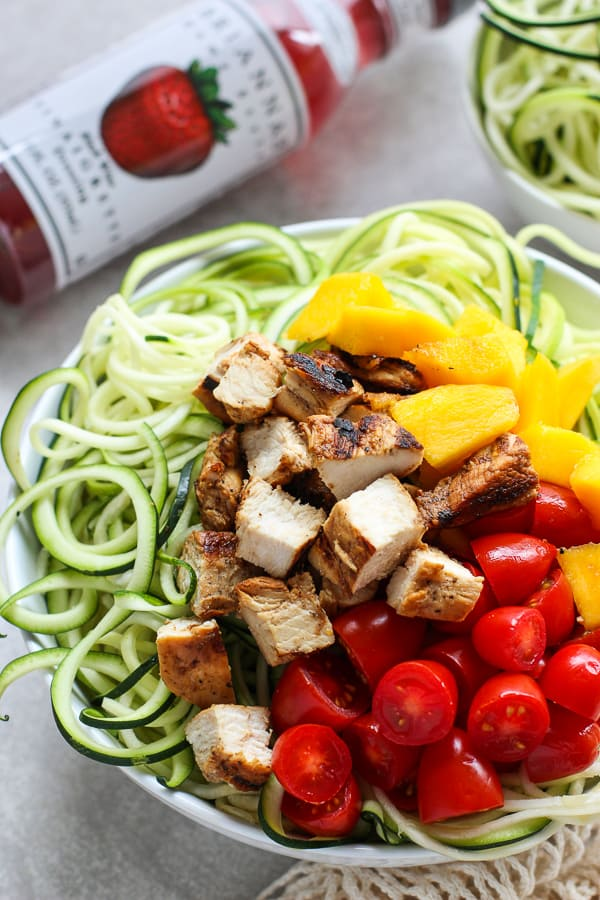 A bowl of zoodles topped with grilled chicken, mango and tomatoes with BRIANNAS dressing on the side