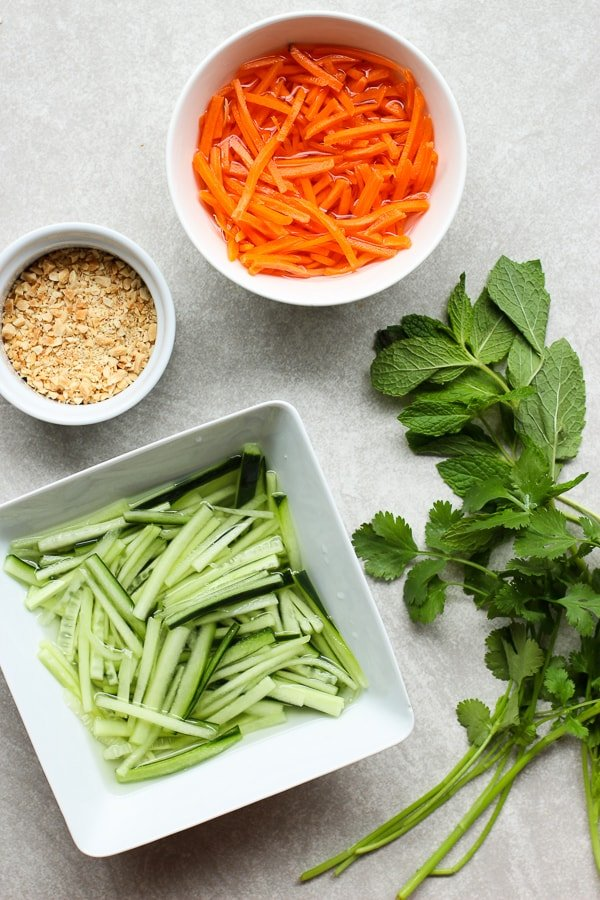 Shredded carrots, peanuts, shredded cucumber, cilantro and mint leaves