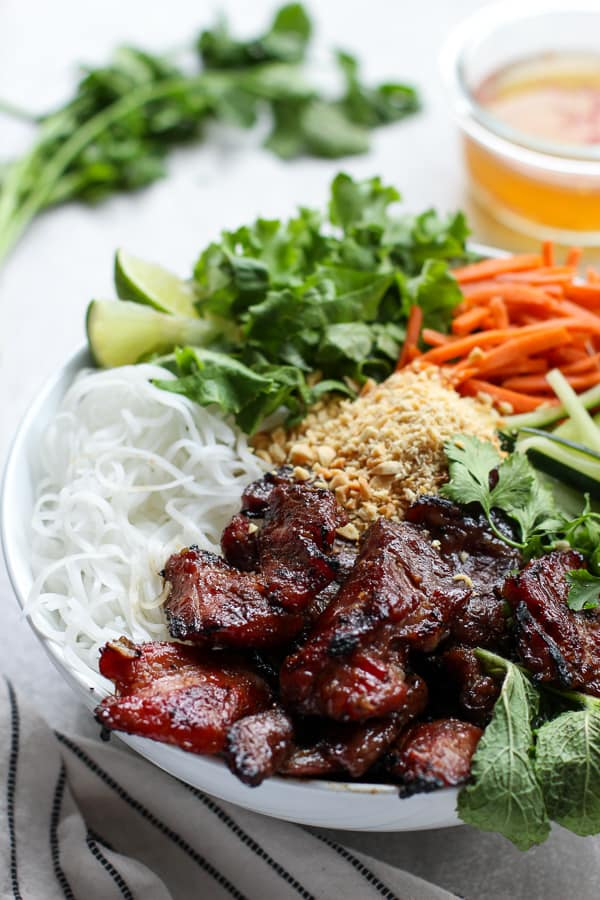 Vietnamese Noodle Bowl filled with vermicelli noodles, grilled pork and veggies, with sauce in the background
