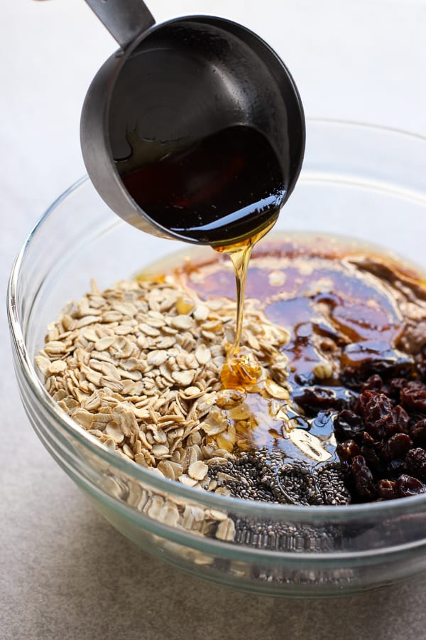 Drizzling honey into a bowl filled with oatmeal, almond butter, raisins, and chia seeds