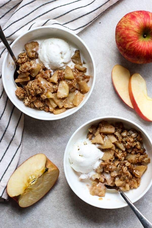 To bowls of Easy Apple Crisp topped with vanilla ice cream