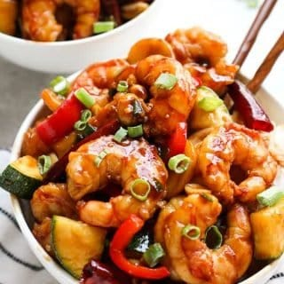 A bowl of Kung Pao Shrimp with chopsticks in the bowl