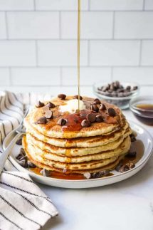 Drizzling maple syrup onto chocolate chip pancakes
