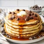 A stack of chocolate chip pancake with maple syrup