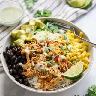 Bowl filled with chicken, corn, black beans, shredded cheese, avocados, cilantro and la wedge of lime
