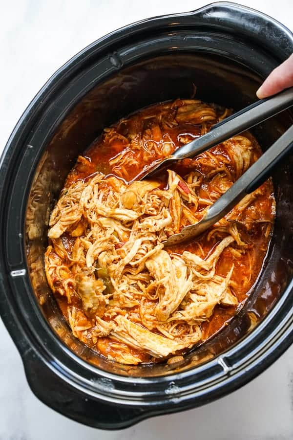 Shredding chicken in a crockpot using a pair of tongs