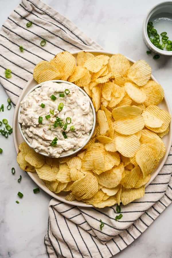 Top down view of a bowl of Caramelized Onion Dip with potato chips
