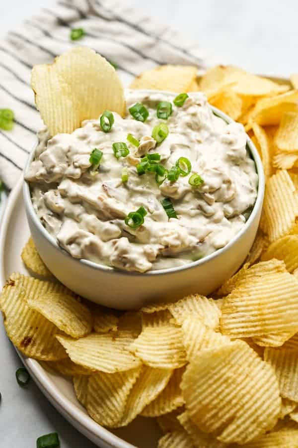 A bowl of dip with lots of potato chips around it