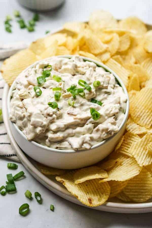 A bowl of Caramelized Onion Dip with potato chips on the side