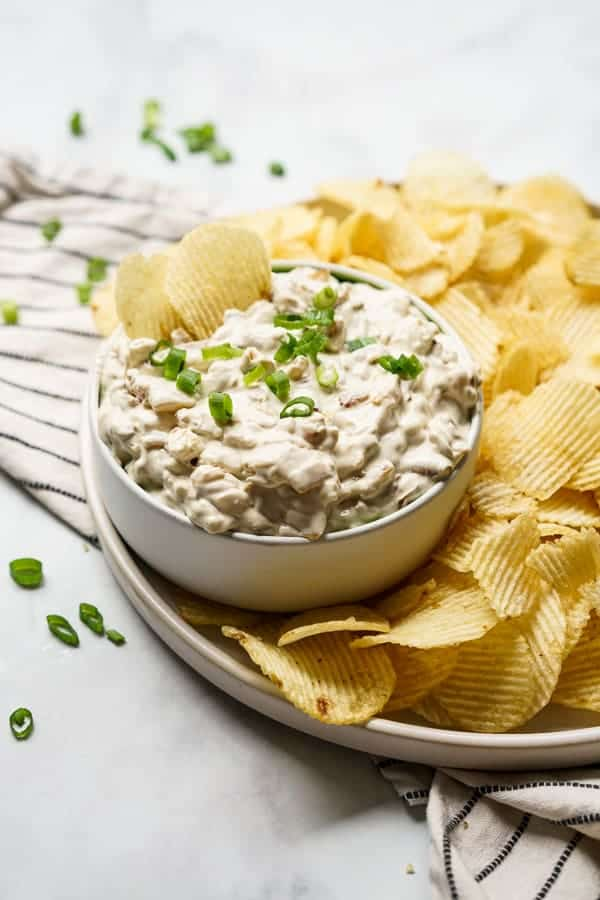 A bowl of caramelized onion dip with potato chips