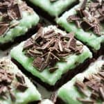 Closeup of chocolate brownies topped with green mint icing and Andes Mint pieces