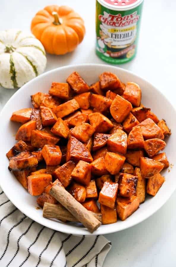 A bowl of Spicy Roasted Sweet Potatoes with spices in the background