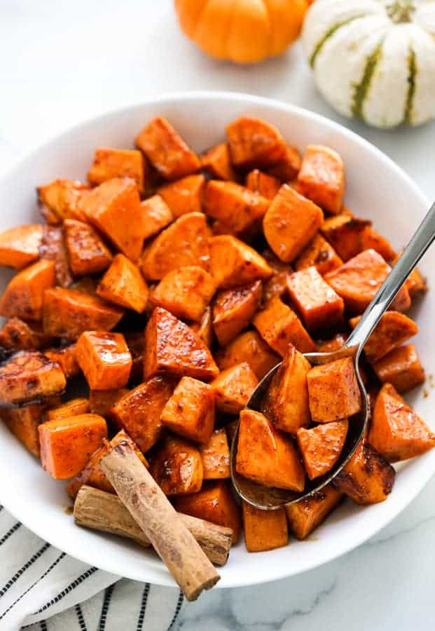 Using a spoon to scoop out some spicy sweet potatoes