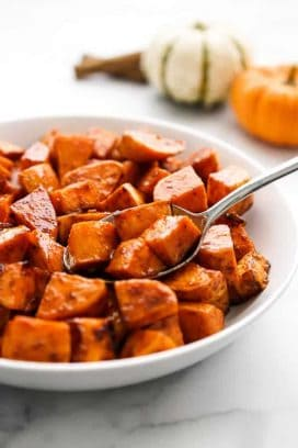 A bowl of sweet potatoes with a spoon