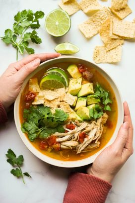 Two hands holding onto a bowl of Instant Pot Chicken Tortilla Soup