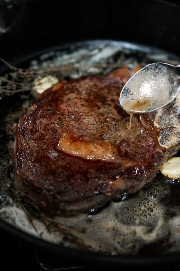 Drizzling butter over steak while searing it