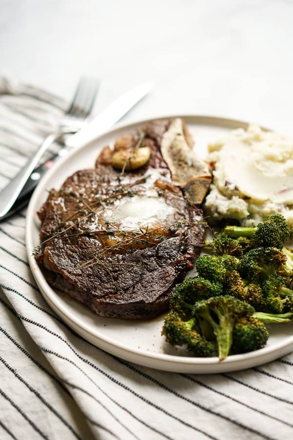 A plate of steak with broccoli and mashed potatoes