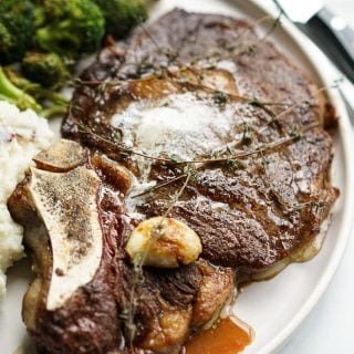 A large piece of Restaurant Style Steak with garlic, fresh thyme and butter