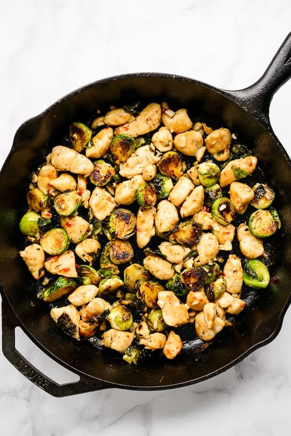 Sauteing Brussels sprouts and chicken on a cast iron skillet