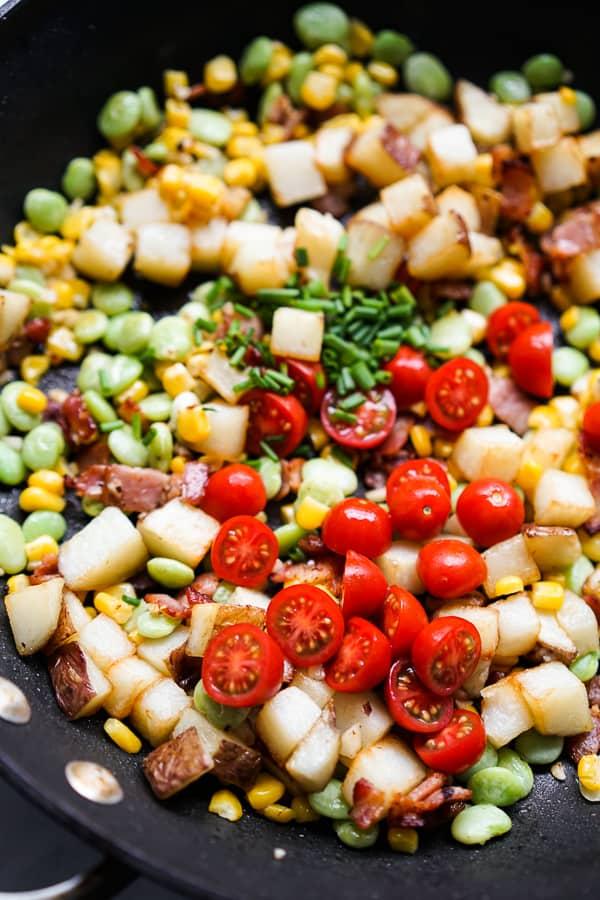 A skillet filled with potatoes, cherry tomatoes, corn and lima beans