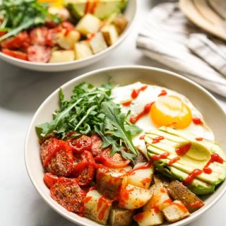 Two savory breakfast bowls filled with roasted potatoes, roasted tomatoes, avocados, egg and arugula