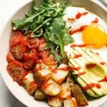 Savory breakfast bowl filled with roasted potatoes, roasted tomatoes, avocados, egg and arugula