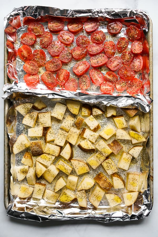 A sheet pan with roasted russet potatoes and roasted tomatoes
