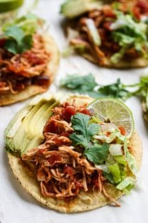 Tostadas topped with shredded chipotle chicken, avocados, cilantro, lettuce and a wedge of lime