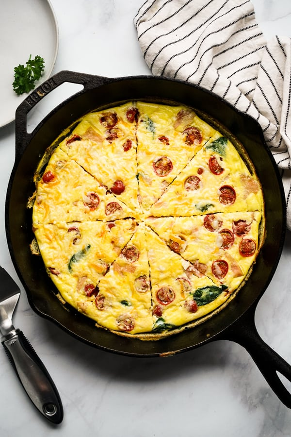 Easy Frittata Recipe with ham, spinach and tomato on a cast iron