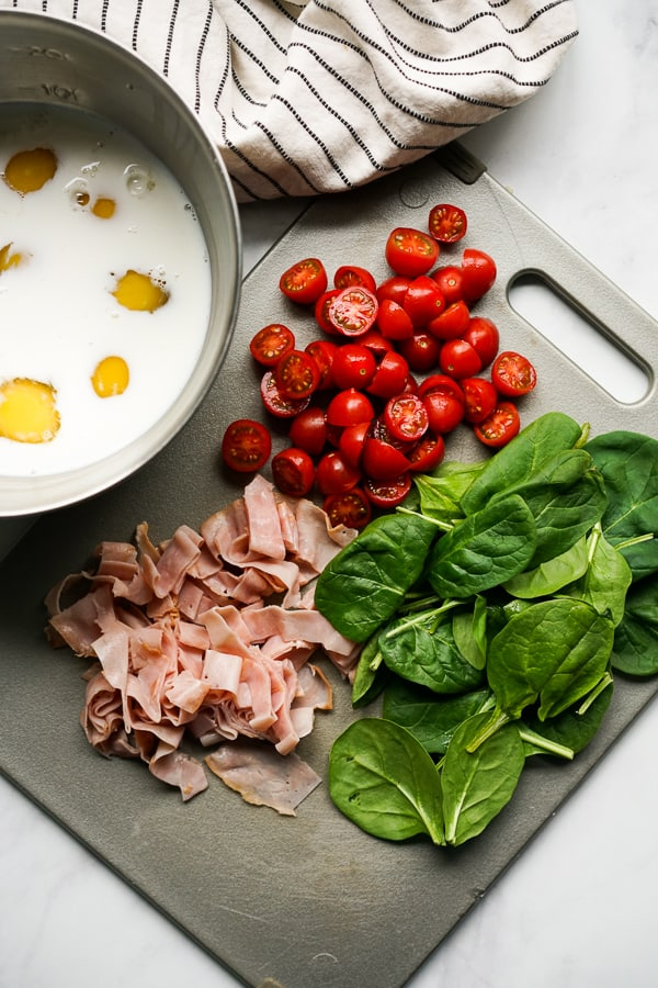 Eggs and milk mixture, cherry tomatoes, ham and spinach