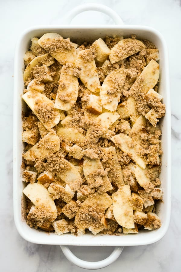 Sliced apple, egg mixture, French bread, and crumble topping in a casserole dish