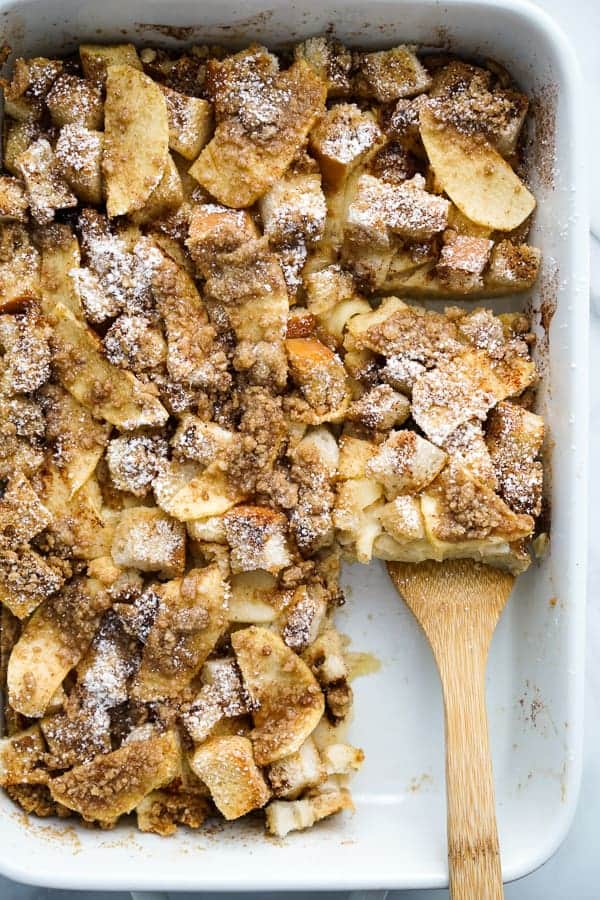 Using a spatula to lift up a square slice of Baked French Toast Casserole from a rectangular dish.