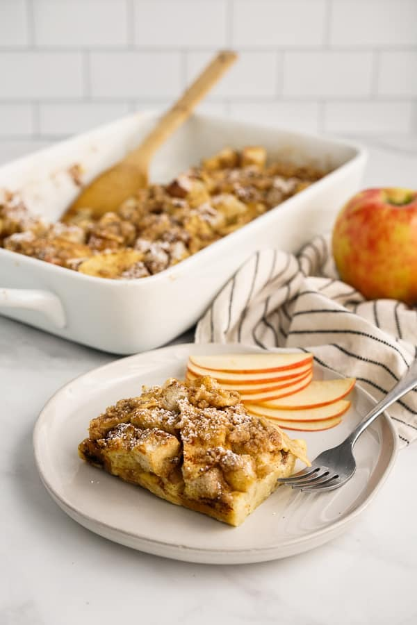 A plate of Apple French Toast with the casserole dish behind it