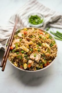 Fried rice with chicken in a bowl, with chopsticks on the bowl