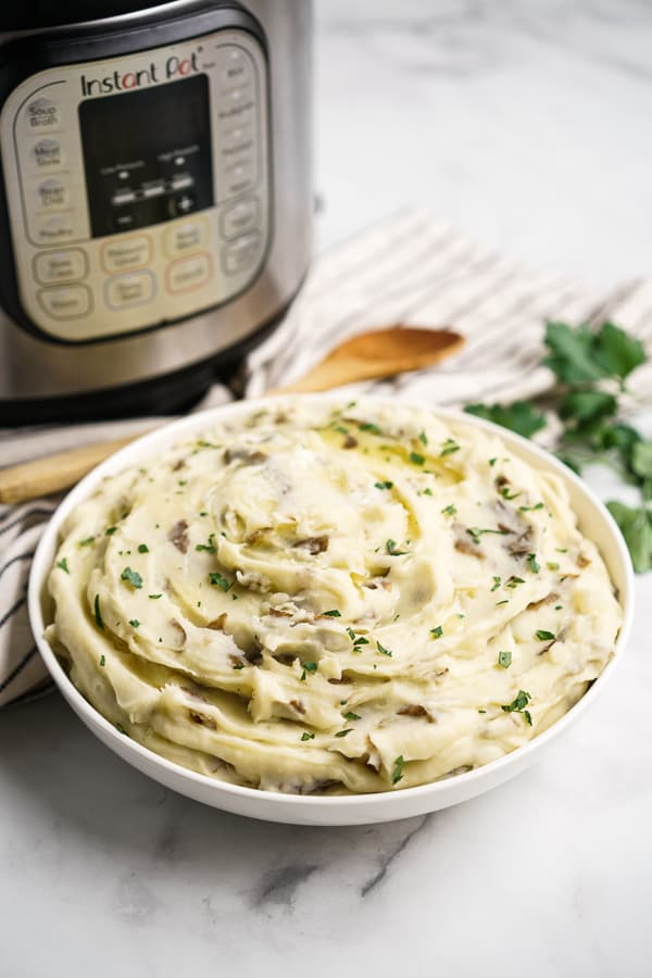 A bowl of garlic mashed potatoes with Instant Pot in the background