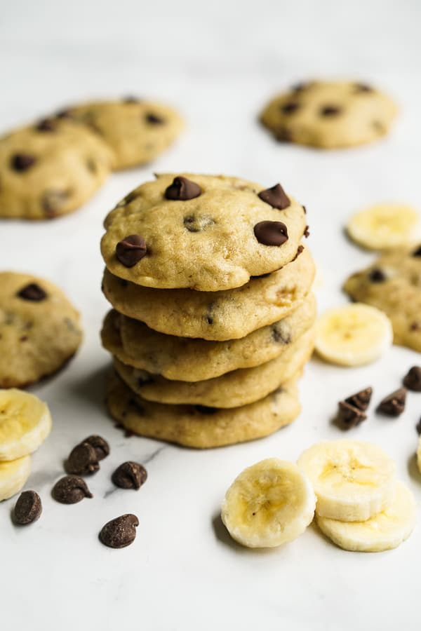 A stack of cookies with more cookies, sliced bananas and chocolate chips around it