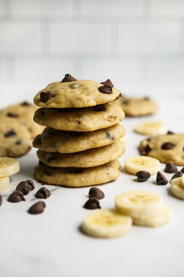 A tall stack of cookies with banana and chocolate chips around it