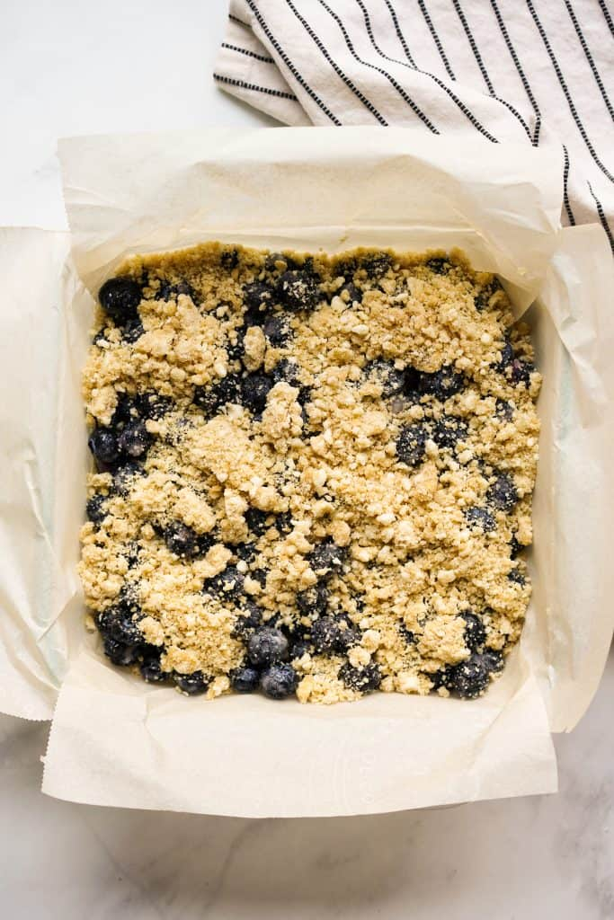 Unbaked blueberry crumble bars on a square dish