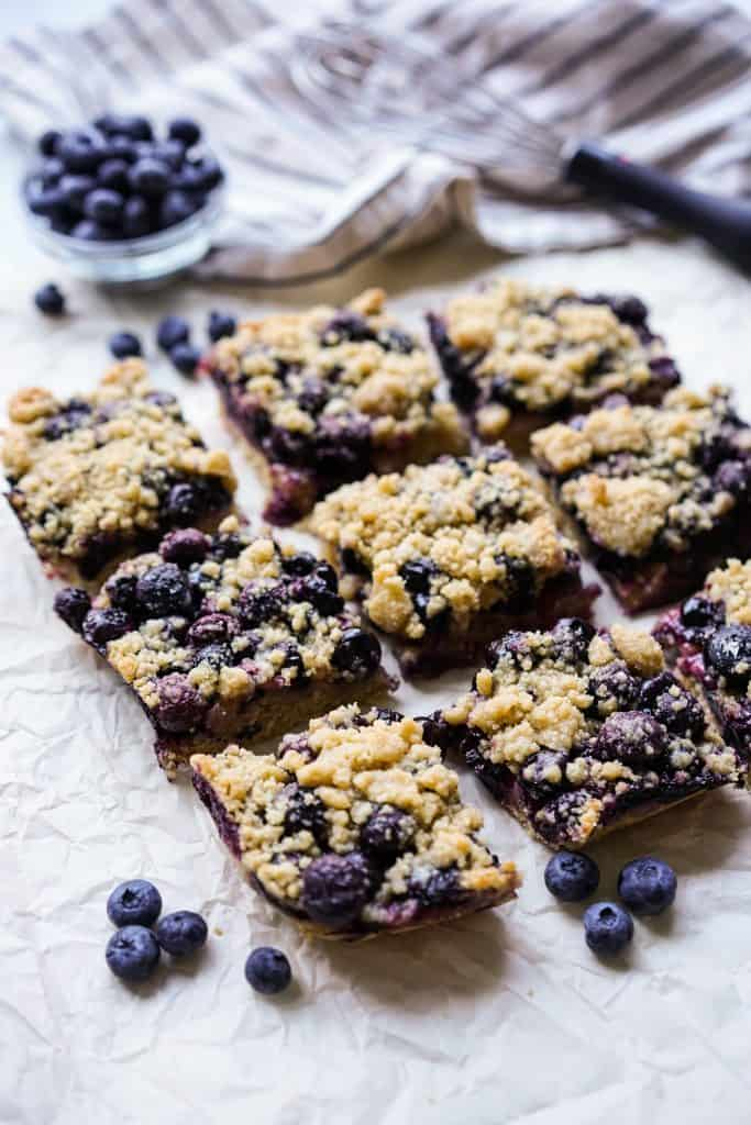 Nine square blueberry crumb bars placed on crinkled parchment paper