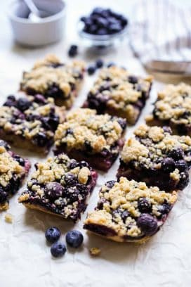 Square blueberry crumble bars on parchment paper with blueberries around it