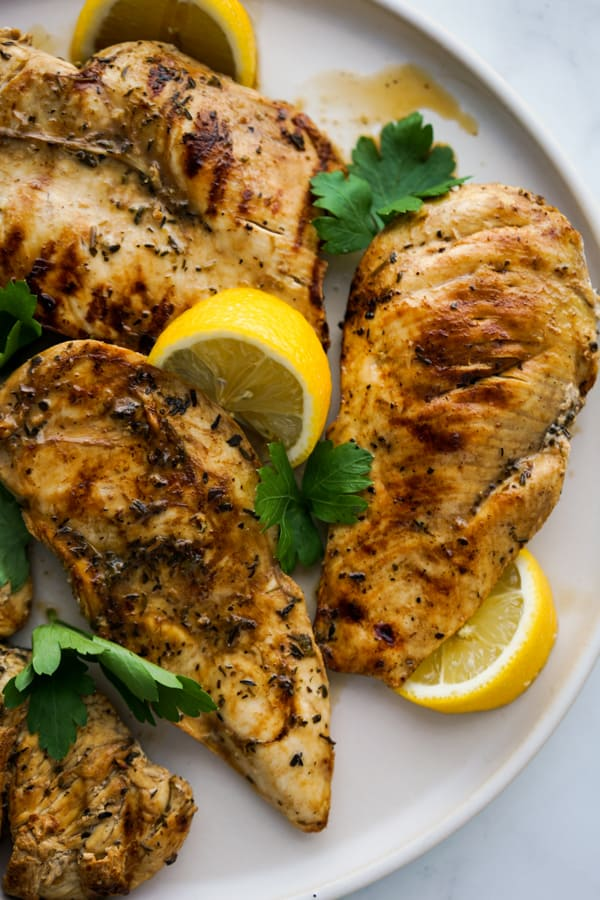 A plate of Lemon Balsamic Grilled Chicken with fresh lemons and parsley