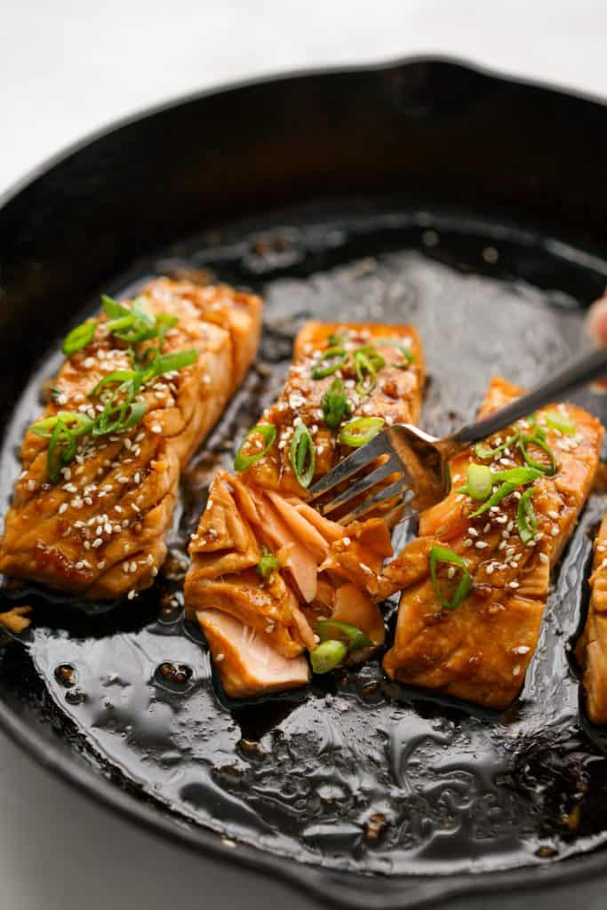 Cutting into a piece of teriyaki salmon
