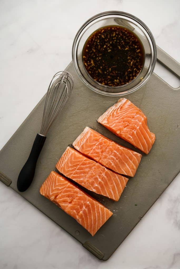 Pieces of raw salmon and a bowl of teriyaki sauce on cutting board