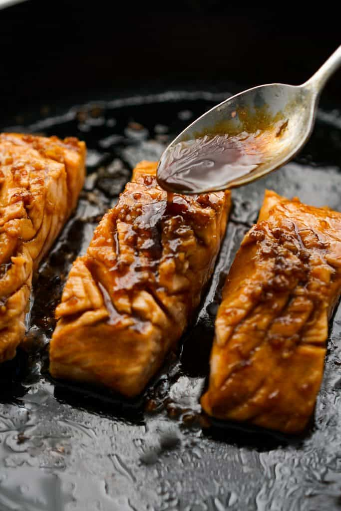 Drizzling teriyaki sauce onto salmon on skillet