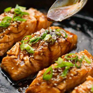 Drizzling teriyaki sauce onto salmon
