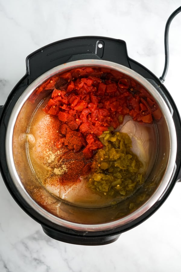 Uncooked chicken, tomatoes, spices, green chilis and chicken broth in the Instant Pot