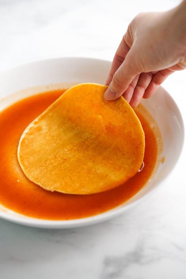 Dip corn tortilla (both sides) into red enchilada sauce